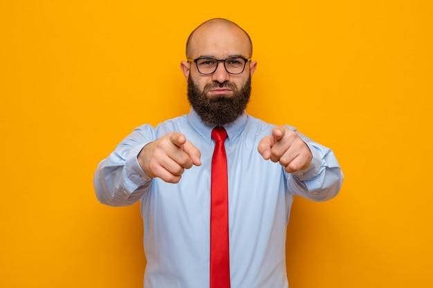 Bärtiger mann in roter krawatte und hemd mit brille, der mit den zeigefingern nach vorne zeigt und selbstbewusst aussieht
