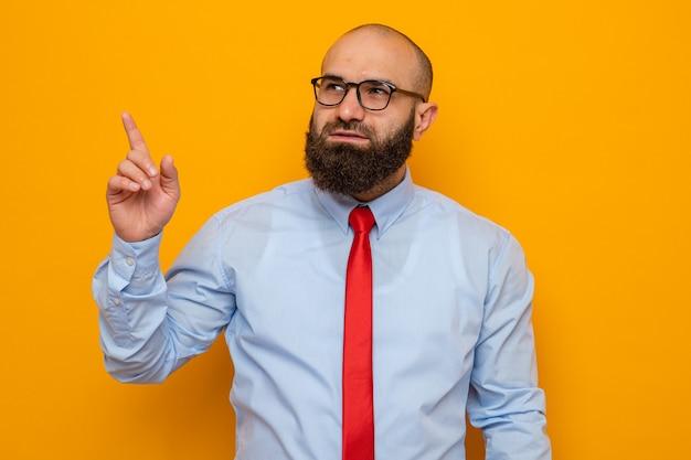 Bärtiger mann in roter krawatte und hemd mit brille, der mit einem lächeln auf einem intelligenten gesicht zur seite schaut und mit dem zeigefinger auf etwas zeigt