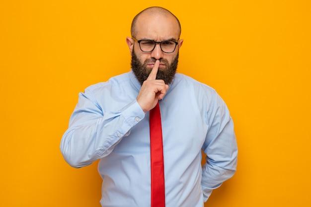 Bärtiger mann in roter krawatte und hemd mit brille, der mit ernstem gesicht aussieht und stillegeste mit dem finger auf den lippen macht