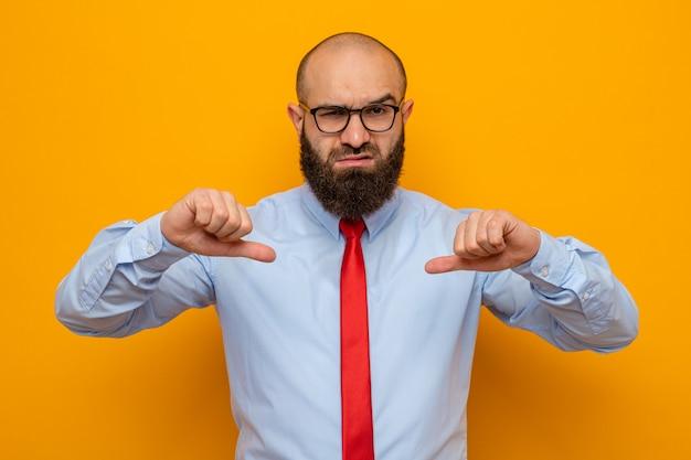 Bärtiger mann in roter krawatte und hemd mit brille, der mit ernstem gesicht schaut und mit daumen auf sich selbst zeigt