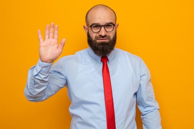 Bärtiger mann in roter krawatte und hemd mit brille, der selbstbewusst mit der hand winkt