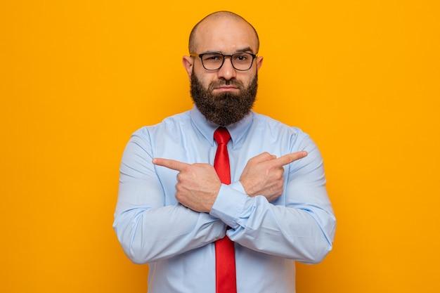 Bärtiger mann in roter krawatte und hemd mit brille und blick in die kamera mit ernstem gesicht, das die hände kreuzt und mit zeigefingern auf die seiten zeigt, die über orangefarbenem hintergrund stehen