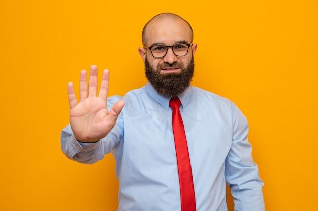 Bärtiger mann in roter krawatte und hemd mit brille und blick in die kamera mit nummer fünf mit handfläche auf orangefarbenem hintergrund