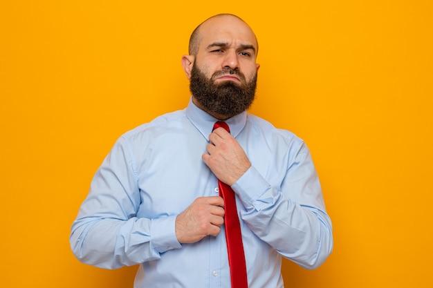 Bärtiger mann in roter krawatte und hemd sieht selbstbewusst aus und berührt und repariert seine krawatte and