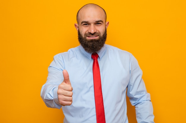 Bärtiger mann in roter krawatte und hemd sieht selbstbewusst lächelnd aus und zeigt daumen nach oben