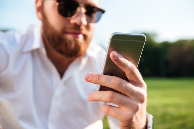 Bärtiger mann in sonnenbrille und hemd, während smartphone verwendet. konzentrieren sie sich auf das telefon