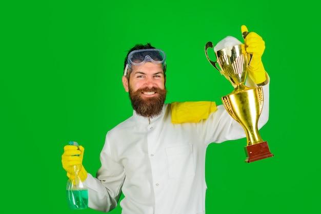 Bärtiger mann in uniform und handschuhen mit reinigungsspray und goldpokal-mann vom profi