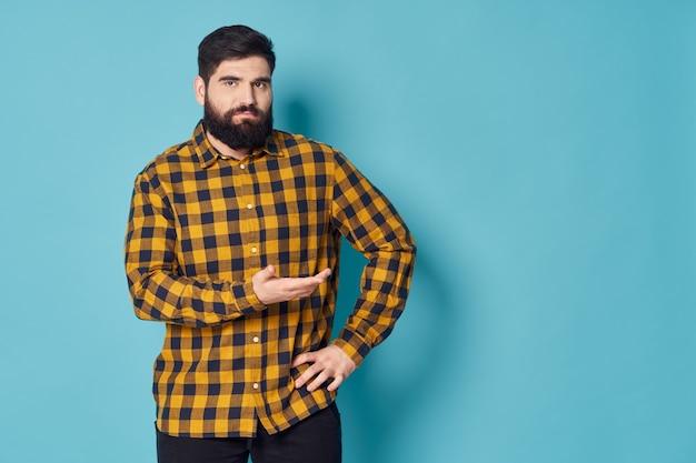Bärtiger mann kariertes hemd gestikuliert mit händen studio