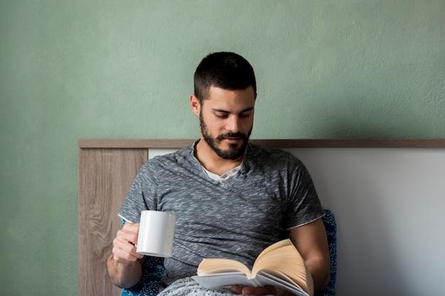 Bärtiger mann liest ein buch und hält eine tasse