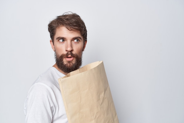 Bärtiger mann mit bastelpaket in den händen beim einkaufen von emotionen heller hintergrund