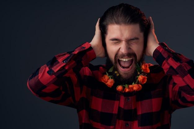 Bärtiger mann mit blumen im bart in einem karierten hemd mit dunklem hintergrund