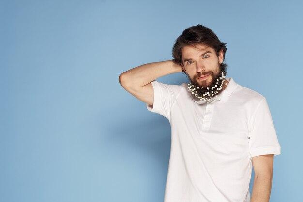 Bärtiger mann mit blumen in seinen haarschmuckspaß weißem t-shirt blauem hintergrund