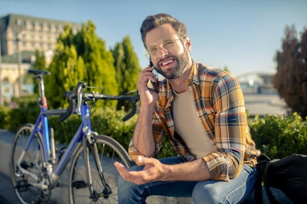 Bärtiger mann mit brille am telefon sprechen
