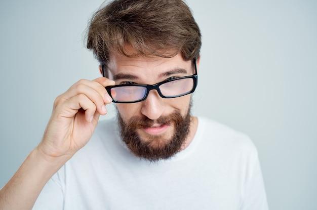 Bärtiger mann mit brille in der hand sehprobleme bei hellem hintergrund