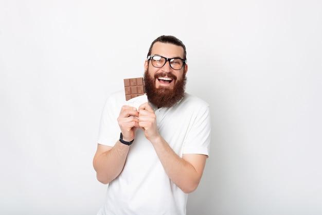 Bärtiger mann mit brille ist in schokolade verliebt, die er hält.
