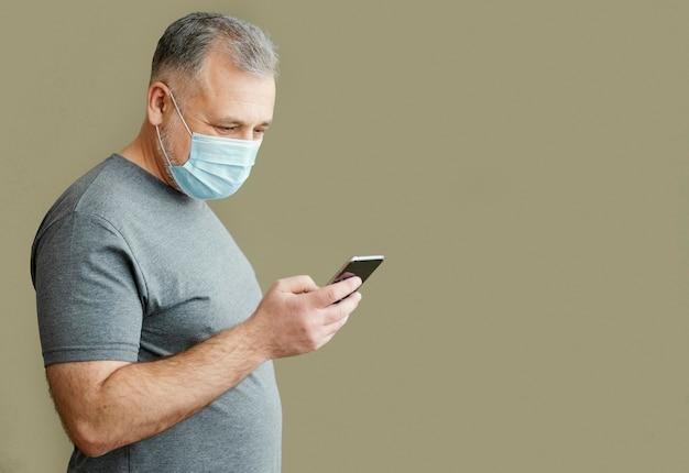 Bärtiger mann mit chirurgischer maske unter verwendung des telefons