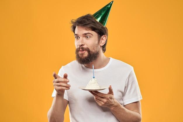 Bärtiger mann mit einem kuchen und in einer kappe, die seinen geburtstag feiert.