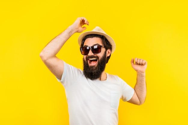Bärtiger mann mit einer positiven stimmung auf gelbem grund Premium Fotos