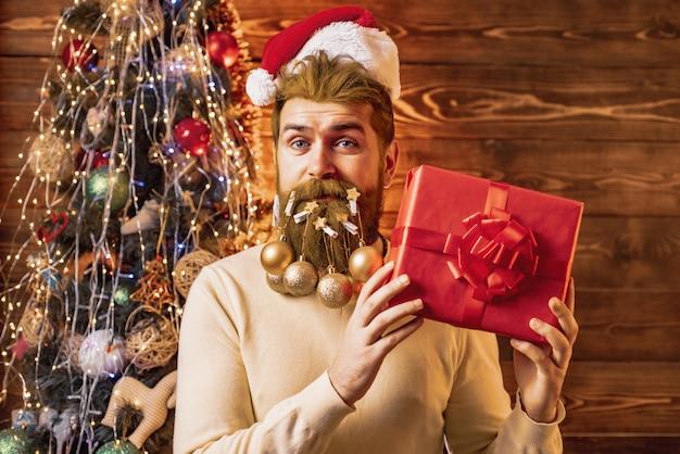 Bärtiger mann mit globen im bart, der ein geschenk hält
