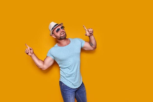 Bärtiger mann mit hut und sonnenbrille zeigt mit dem finger nach oben