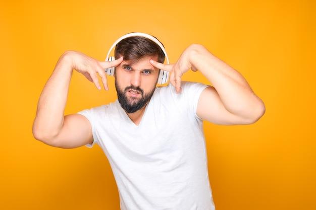 Bärtiger mann mit kopfhörern führt emotional tanzbewegungen zur musik durch.