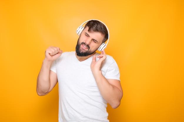 Bärtiger mann mit musikkopfhörern schloss die augen und hört musik.