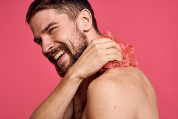Bärtiger mann mit nackten schultern mit einem waschlappen-badezimmer mit sauberer haut.