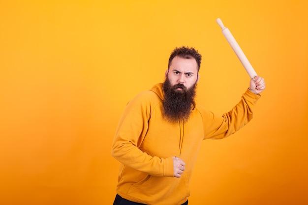 Bärtiger mann mit paddel, als wäre er ein baseballschläger auf gelbem hintergrund. aggressiver ausdruck.