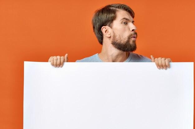 Bärtiger mann mit plakat in der hand auf orange hintergrund
