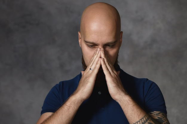 Bärtiger mann mit rasiertem kopf, der erkältet ist und hände an der nase hält, als würde er niesen. glatzköpfiger mann, der sich deprimiert fühlt und das gesicht bedeckt, nachdenkt und nach einer lösung für das problem sucht. körpersprache