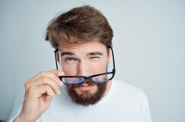 Bärtiger mann mit schlechter sehkraft gesundheitliche probleme isolierter hintergrund. foto in hoher qualität