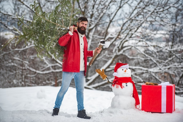 Bärtiger mann mit schneemann trägt weihnachtsbaum im wald. ein hübscher junger mann mit schneemann