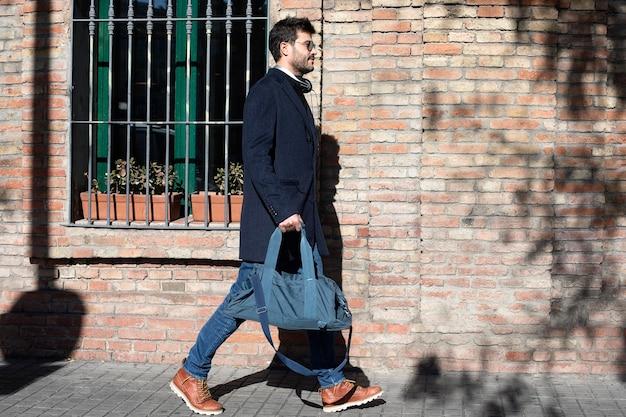 Bärtiger mann mit sonnenbrille und freizeitkleidung, der eine sporttasche trägt, während er auf der straße geht