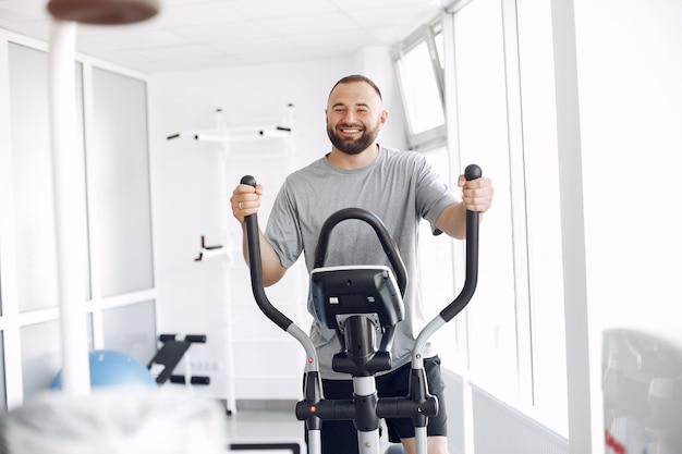 Bärtiger mann mit spinbike im physiotherapieraum