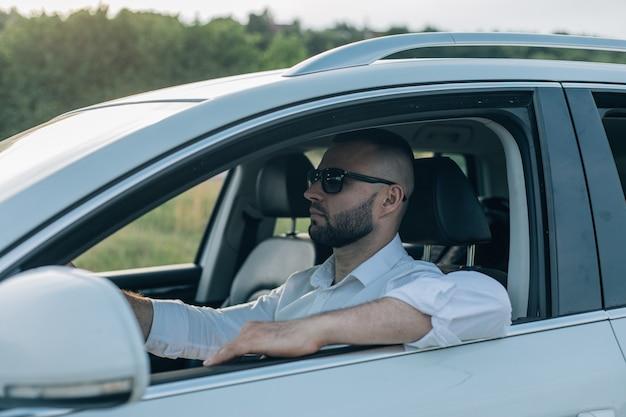 Bärtiger mann mit stil und status. hübscher junger mann im vollen anzug, der beim fahren eines weißen autos lächelt.