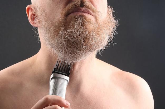 Bärtiger mann mit trimmer zum einstellen des bartes in der hand