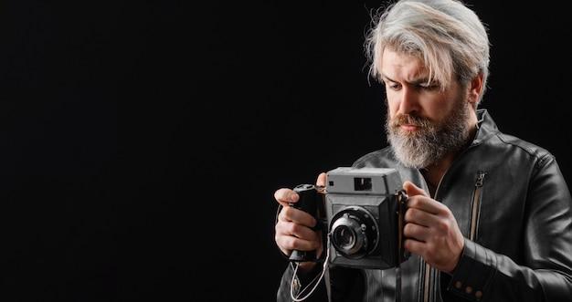 Bärtiger mann mit vintage-fotokamera. stilvoller fotograf in lederjacke mit retro-kamera.