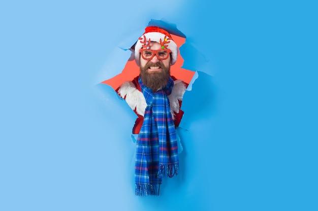 Bärtiger mann mit weihnachtsmütze und partybrille durch loch in papierwerbung weihnachtsrabattverkauf