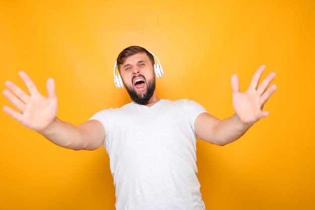 Bärtiger mann mit weißen kopfhörern singt laut und gestikuliert mit den händen.