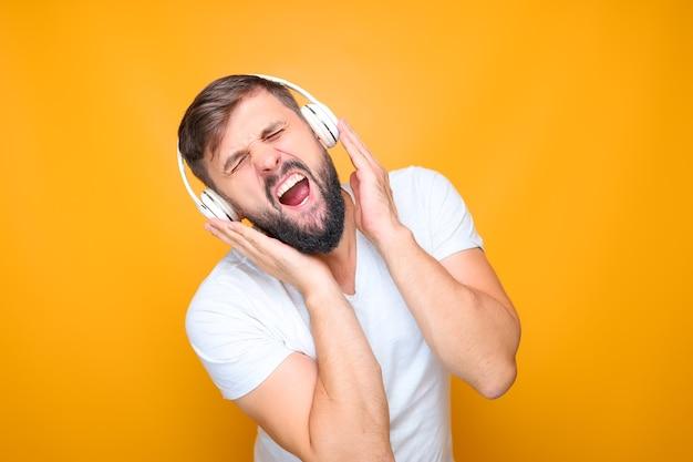 Bärtiger mann mit weißen musikkopfhörern hört musik und singt gleichzeitig.