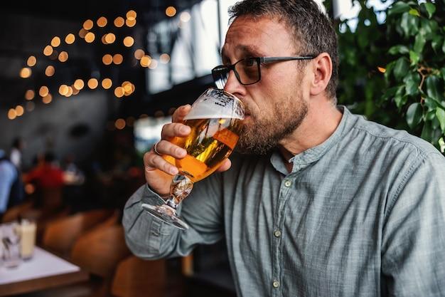 Bärtiger mann mittleren alters, der in einer bar sitzt und frisches kaltes helles bier trinkt. es ist zeit, sich nach der arbeit zu entspannen. haben sie immer etwas zeit für sich.