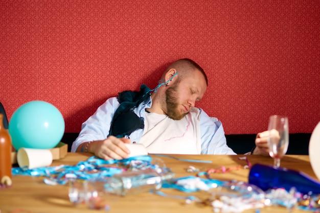 Bärtiger mann schläft am tisch in einem unordentlichen zimmer mit mädchenunterwäsche, büstenhalter nach junggesellenabschied