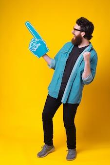Bärtiger mann schreit ja, während er blauen fächerschaumhandschuh trägt