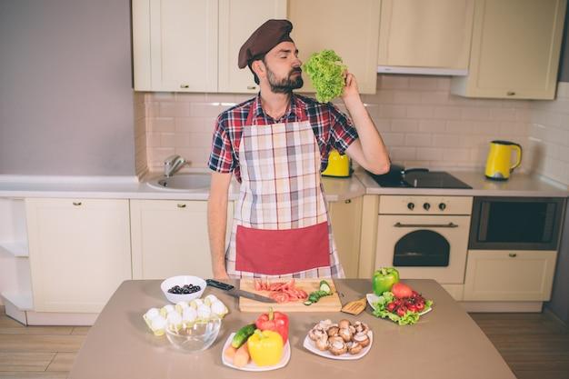 Bärtiger mann steht und riecht an laub. er hält die augen geschlossen. der mensch ist ernst und konzentriert. guy steht in der küche. er bereitet essen zu.