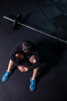 Bärtiger mann übt training im fitness-fitness-breaking-relax nach dem trainingssport mit hantel.