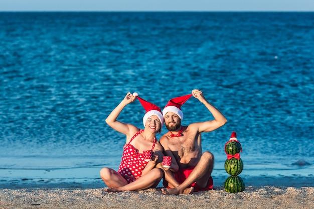 Bärtiger mann und mädchen in weihnachtskleidung sitzen am meeresstrand mit tassen in den händen und schneemann aus wassermelonen. sommer weihnachtsfeier.