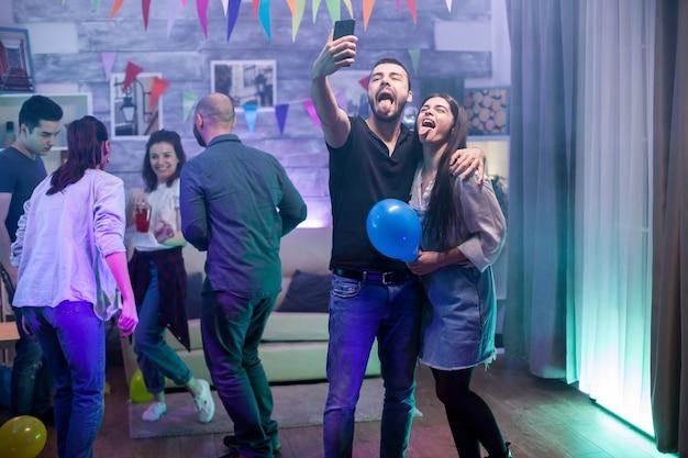 Bärtiger mann und seine freundin mit herausgestreckter zunge machen ein selfie, während sie mit ihren freunden feiern.