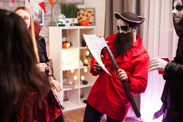 Bärtiger mann verkleidet wie ein pirat, der eine axt hält, während er halloween mit seinen monsterfreunden feiert.