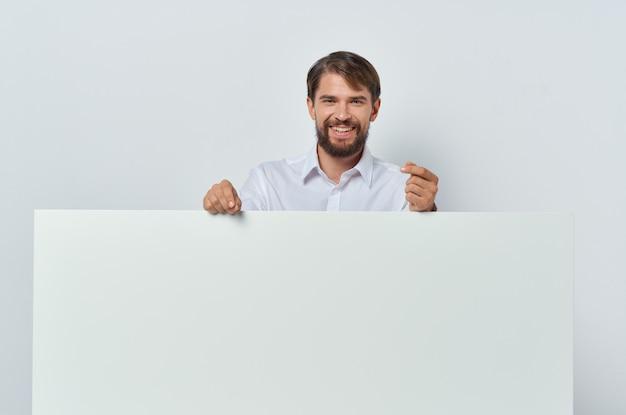 Bärtiger mann weißes banner in der hand leeres blatt präsentation isolierten hintergrund. foto in hoher qualität