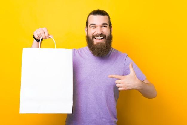 Bärtiger mann zeigt auf eine weiße große einkaufstasche.